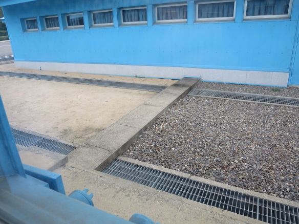 The concrete slab is a country border. The pebbly ground is South Korea and the plain sandy ground is North Korea.
